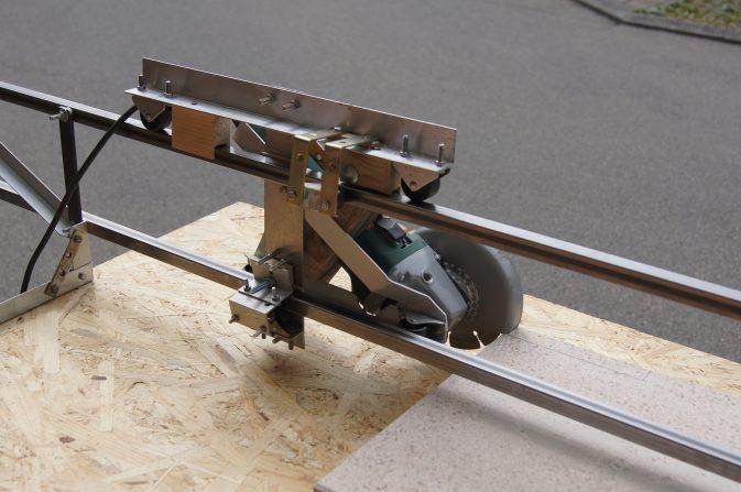 Der Winkelschleifer ist auf einen Laufwagen montiert. Dieser läuft auf zwei, kalt gezogenen 4-Kant-Profilen, die parallel verlaufen